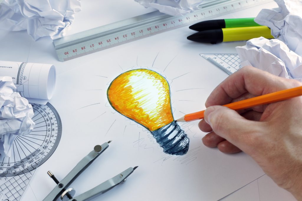Designer drawing a light bulb symbolizing intellectual property in Milwaukee